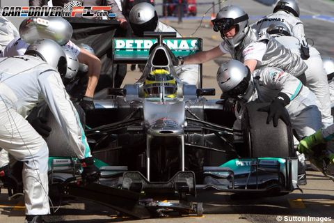 Helmet, Automotive tire, Personal protective equipment, Open-wheel car, Formula racing, Motorsport, Sports gear, Team, Formula one, Race track,