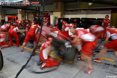 Human leg, Automotive tire, Carmine, Helmet, Sports gear, Calf, Race track, Fan, Pit stop, Hip,