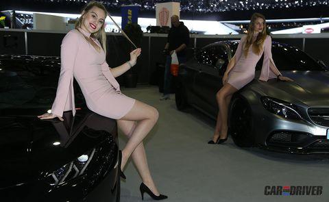 Automotive design, Leg, Land vehicle, Event, Human leg, Shoe, High heels, Headlamp, Automotive lighting, Exhibition,
