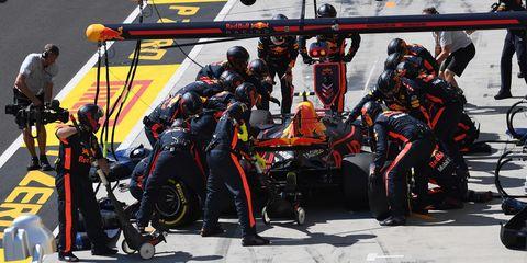 Tire, Automotive tire, Motorsport, Helmet, Race track, Team, Pit stop, Automotive wheel system, Sports gear, Racing,