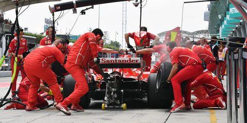 Pit stop, Race track, Sport venue, Race car, Formula one, Red, Formula one tyres, Vehicle, Automotive tire, Team,