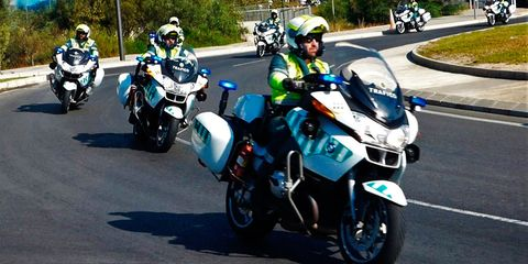 Land vehicle, Vehicle, Motorcycle, Motorcycle racer, Motorcycling, Motorcycle helmet, Motor vehicle, Road racing, Car, Police,