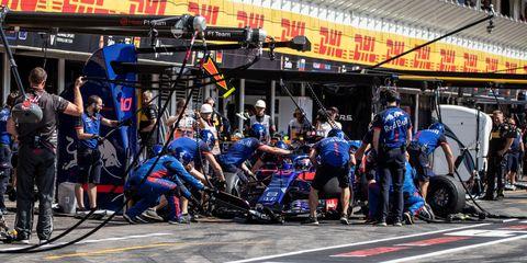 Automotive tire, Team, Video camera, Pit stop, Television crew, Crew, Race track, Automotive wheel system, Film crew, Camera operator,