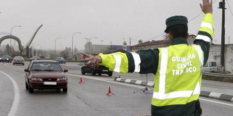 Motor vehicle, Road, Road surface, Workwear, High-visibility clothing, Asphalt, Automotive parking light, Automotive mirror, Street light, Job,
