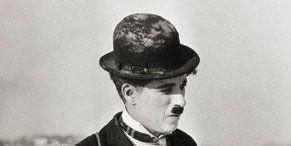 Hat, Collar, Formal wear, Sitting, Headgear, Vintage clothing, Blazer, Monochrome, Bag, Portrait,