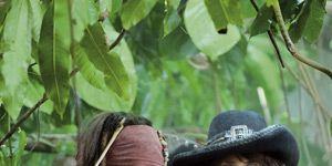 Human, Mouth, Hat, Headgear, Youth, Long hair, Costume accessory, Sun hat, Fedora, Jungle,