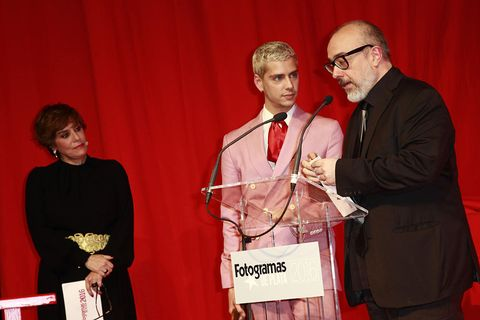 Glasses, Microphone, Dress shirt, Audio equipment, Tie, Red, Public speaking, Formal wear, Award ceremony, Award,