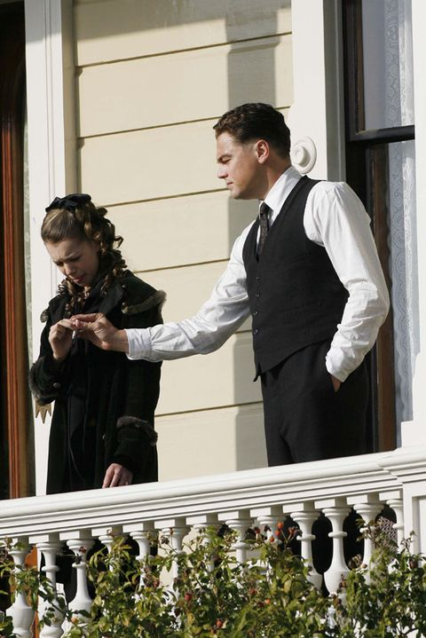 Dress shirt, Ceremony, Baluster, Hair accessory, Love, Balcony, Suit trousers, Wedding dress, Bride, Holding hands,