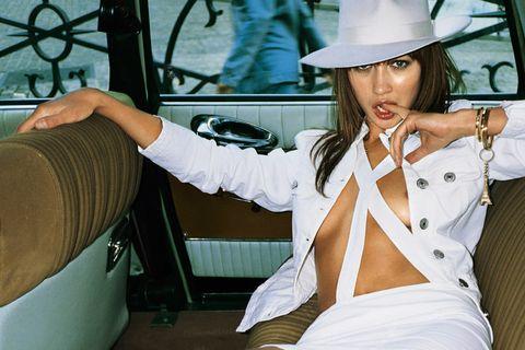 Hat, Dress shirt, Sun hat, Steering wheel, Steering part, Windshield, Vehicle door, Fedora, Model, Cuff,