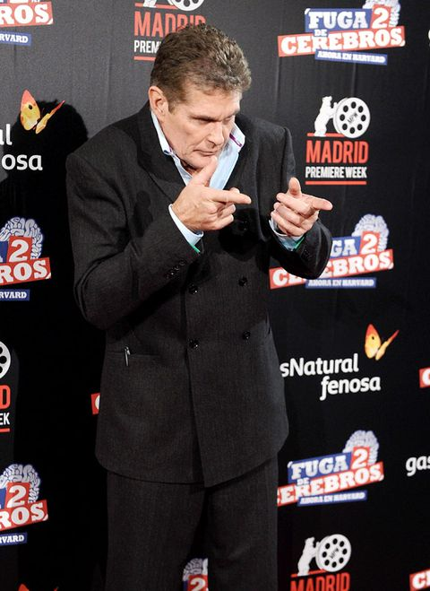 Suit, Coat, Formal wear, Logo, Blazer, Premiere, White-collar worker, Tuxedo, Carpet, Pocket,