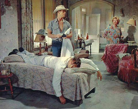 Human, Lighting, Room, Hat, Sun hat, Linens, Vintage clothing, Fedora, Bedding, Bed,