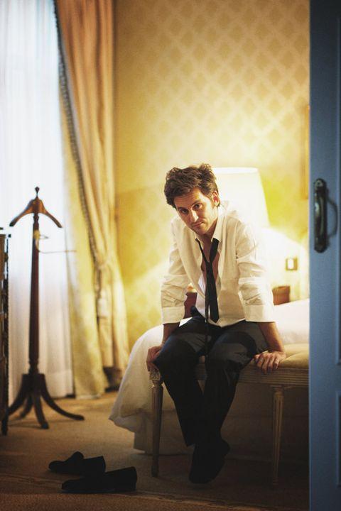 Shoe, Sitting, Curtain, Door, Door handle, Suit trousers, Home door, Lamp, Shadow,