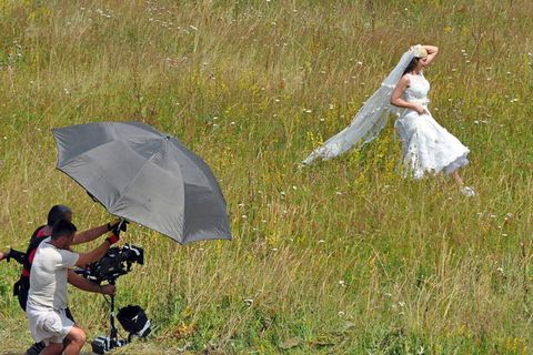 Human, Umbrella, People in nature, Dress, Grassland, Bridal clothing, Video camera, Bride, Gown, Meadow,