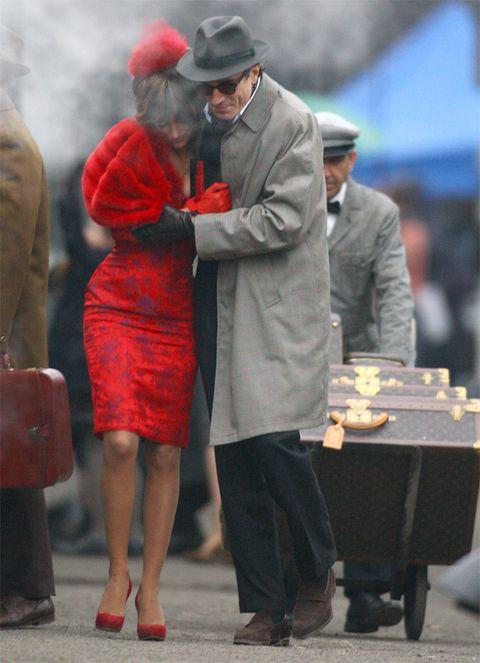 Standing, Red, Hat, Coat, Dress, Conversation, Sun hat, Love, Overcoat, One-piece garment,