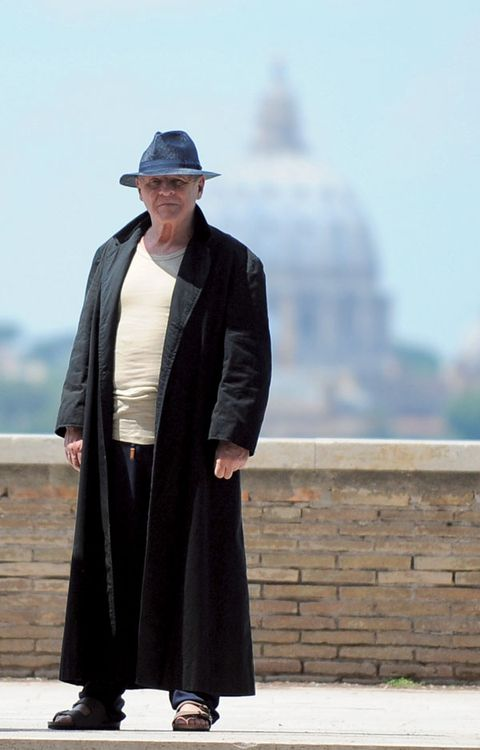 Sleeve, Hat, Standing, Headgear, Street fashion, Sun hat, Costume, Sandal, Fedora, Overcoat,