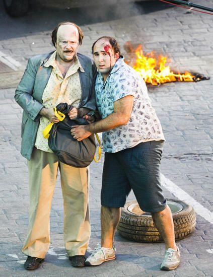Human, T-shirt, Bag, Temple, Street fashion, Fire, Slipper, Luggage and bags, Beard, Flame,