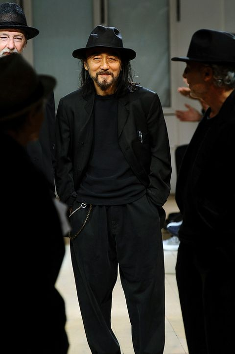 Hat, Facial hair, Sleeve, Trousers, Shirt, Standing, Outerwear, Style, Jacket, Formal wear,