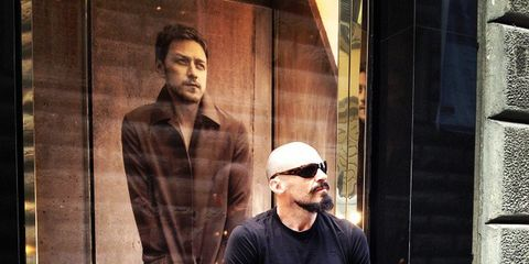 Standing, Facial hair, Street fashion, Beard, Bag, Denim, Moustache, Pocket, Baggage, Brick,
