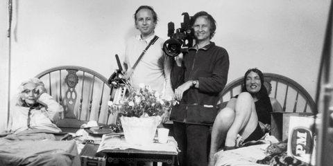 Human, Smile, Room, Comfort, Camera, Sitting, Film camera, Flowerpot, Vintage clothing, Houseplant,