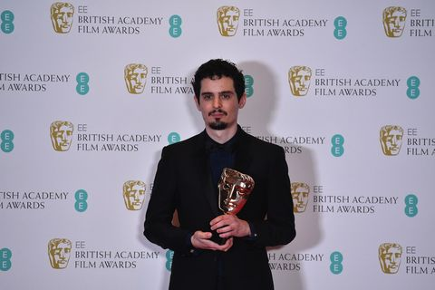 Facial hair, Coat, Suit, Logo, Beard, Blazer, Award, Award ceremony, Moustache, Suit trousers,