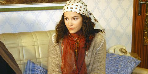 Mouth, Sitting, Couch, Comfort, Headgear, Living room, Headpiece, Picture frame, Lap, Bonnet,