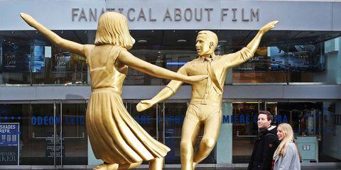 Human, Human body, Sculpture, Interaction, Waist, Gesture, Statue, Blond, Abdomen, One-piece garment,
