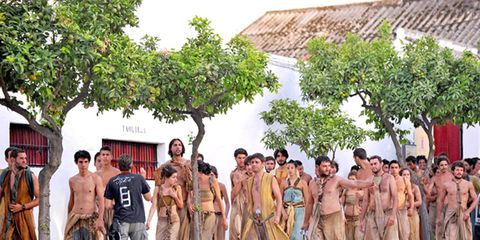People, Human body, Standing, Barechested, Community, Roof, Temple, Muscle, Village, Tribe,