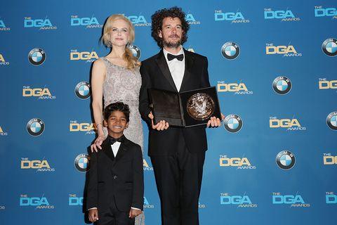 Coat, Award, Award ceremony, Suit trousers, Beard, Ceremony, Bow tie, Tuxedo, Carpet, Button,