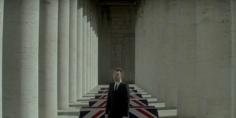 Standing, Formal wear, Column, Blazer, Shadow, Fictional character, Tuxedo, Flag,