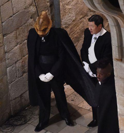 Formal wear, Temple, Fur, Costume accessory, Costume design, Cloak, Costume, Tuxedo, Suit trousers, Ceremony,