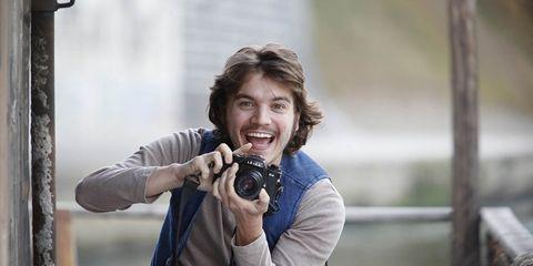 Human, Human body, Single-lens reflex camera, Hand, Camera, Sitting, Facial hair, Moustache, Tooth, Digital camera,