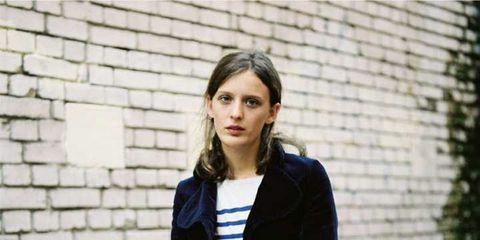 Sleeve, Photograph, Denim, Standing, Jeans, Collar, Jacket, Street fashion, Brick, Blazer,