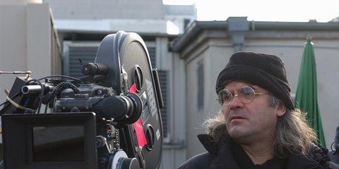 Eyewear, Glasses, Jacket, Video camera, Outerwear, Cap, Filmmaking, Camera, Cameras & optics, Television crew,