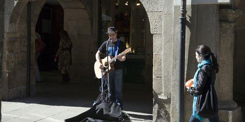 Musical instrument, Human body, Musician, Jacket, Standing, Plucked string instruments, Guitarist, Guitar, Coat, String instrument,