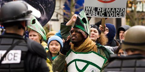 Green, Crowd, Headgear, Team, Public event, Helmet, Law enforcement, Security, Police officer, Protest,