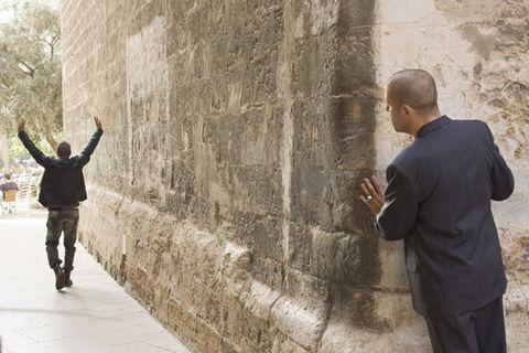 Standing, Wall, Jacket, Temple, Street fashion, Sidewalk, Pedestrian, Walking, Gesture,
