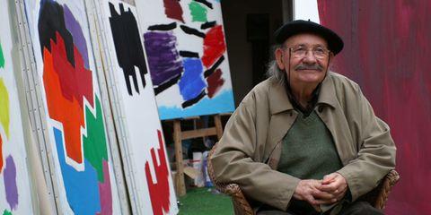 Glasses, Hat, Sitting, Artist, Paint, Art paint, Facial hair, Sun hat, Moustache, Visual arts,