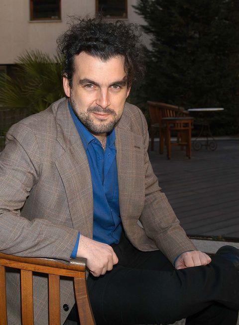 Sitting, Facial hair, Beard, Dress shirt, Blazer, Comfort, Moustache, Lap, Suit trousers, Top,
