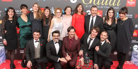 Clothing, Smile, Coat, Event, Trousers, Dress, Red, Social group, Suit, Outerwear,