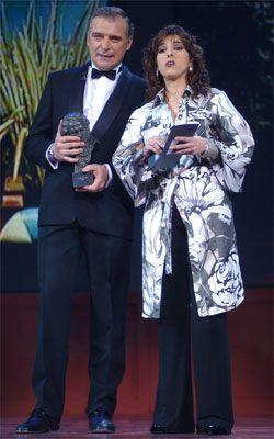 Shoe, Suit trousers, Coat, Collar, Formal wear, Suit, Wine glass, Blazer, Stemware, Drink,