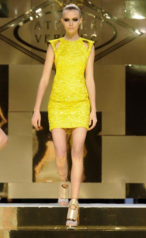 Fashion show, Yellow, Human leg, Shoulder, Dress, Joint, Fashion model, Style, Runway, One-piece garment,