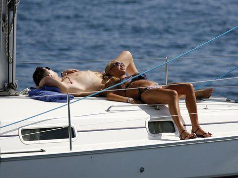 Sun tanning, Luxury yacht, Boat, Yacht, Vehicle, Bikini, Boating, Vacation, Muscle, Swimwear,