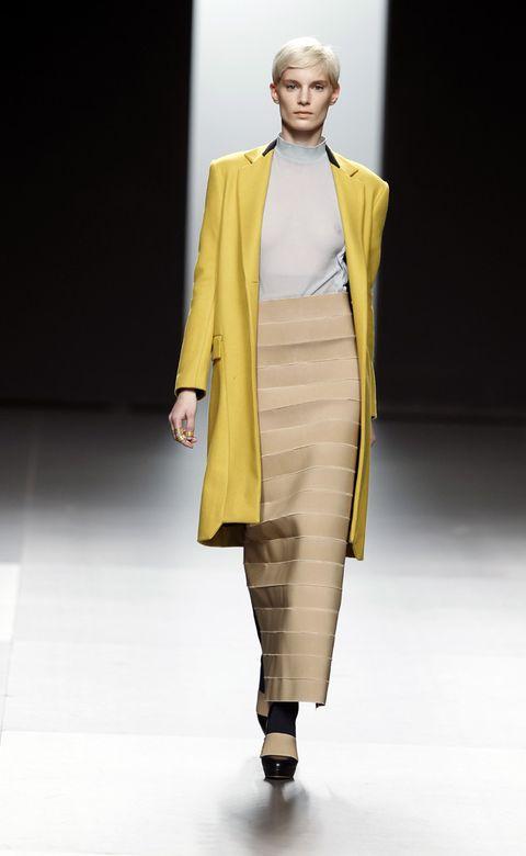 Clothing, Yellow, Human body, Fashion show, Shoulder, Joint, Outerwear, Runway, Coat, Fashion model,