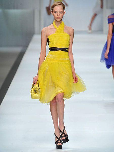 Yellow, Fashion show, Shoulder, Human leg, Dress, Joint, Fashion model, Runway, Waist, One-piece garment,