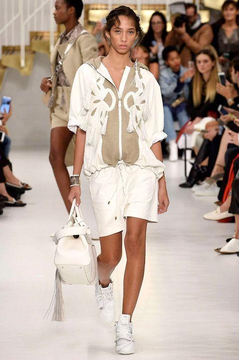 Fashion model, Fashion, Fashion show, White, Runway, Clothing, Shoulder, Shorts, Public event, Fashion design,