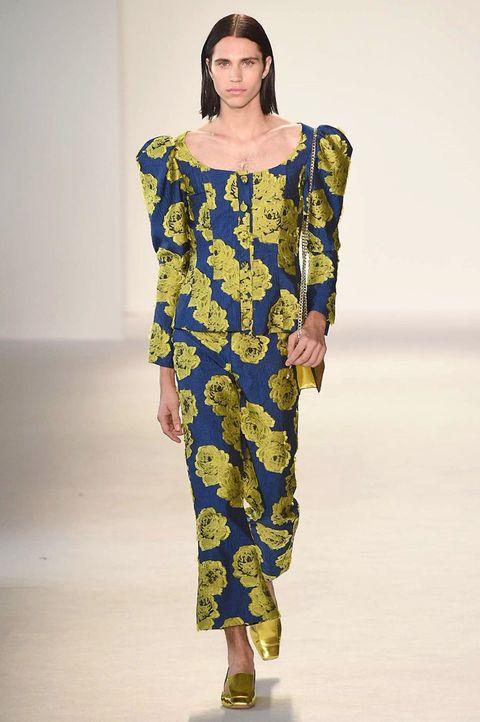 Fashion model, Fashion show, Runway, Fashion, Clothing, Shoulder, Yellow, Fashion design, Joint, Dress,
