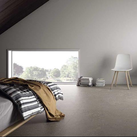 dormitorio moderno con suelo oscuro de gres porcelánico inalco, de la serie masai de ascer