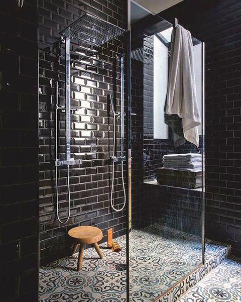 baño ducha con azulejos metro en negro y suelo hidráulico
