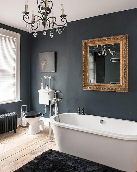baño con las paredes negras y suelo de madera