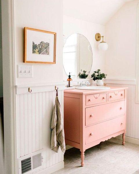 cuarto de baño con mueble de lavabo reciclado en rosa